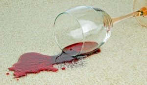 A spilled glass of red wine on a carpet