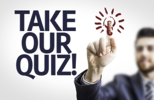 Business man pointing the text: Take Our Quiz