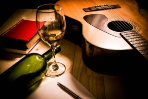 Guitar with Red Book and Wine on a wooden table.