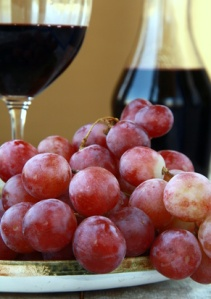 large red ripe grapes and wine on the natural background
